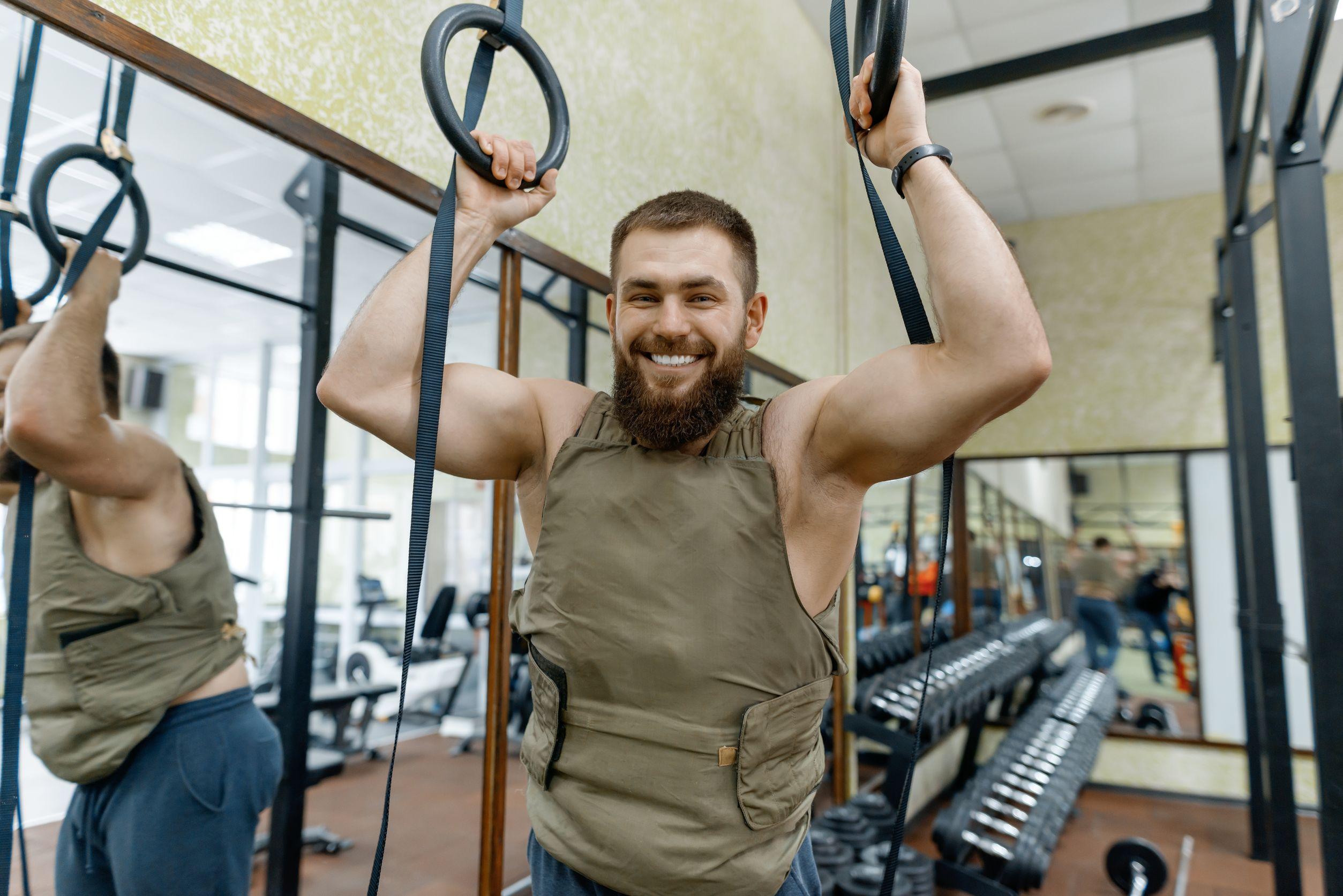 hombre barbudo caucásico musculoso vestido con chaleco lastrado en el gimnasio