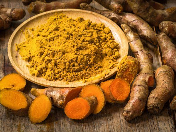 60448329 – fresh turmeric roots with turmeric powder