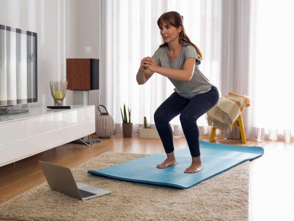 Tiro integral de una mujer haciendo ejercicio en casa