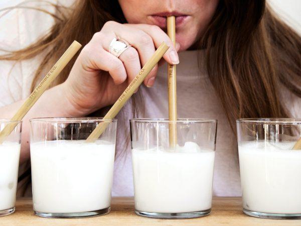 Mujer bebieno leche con pajillas de madera