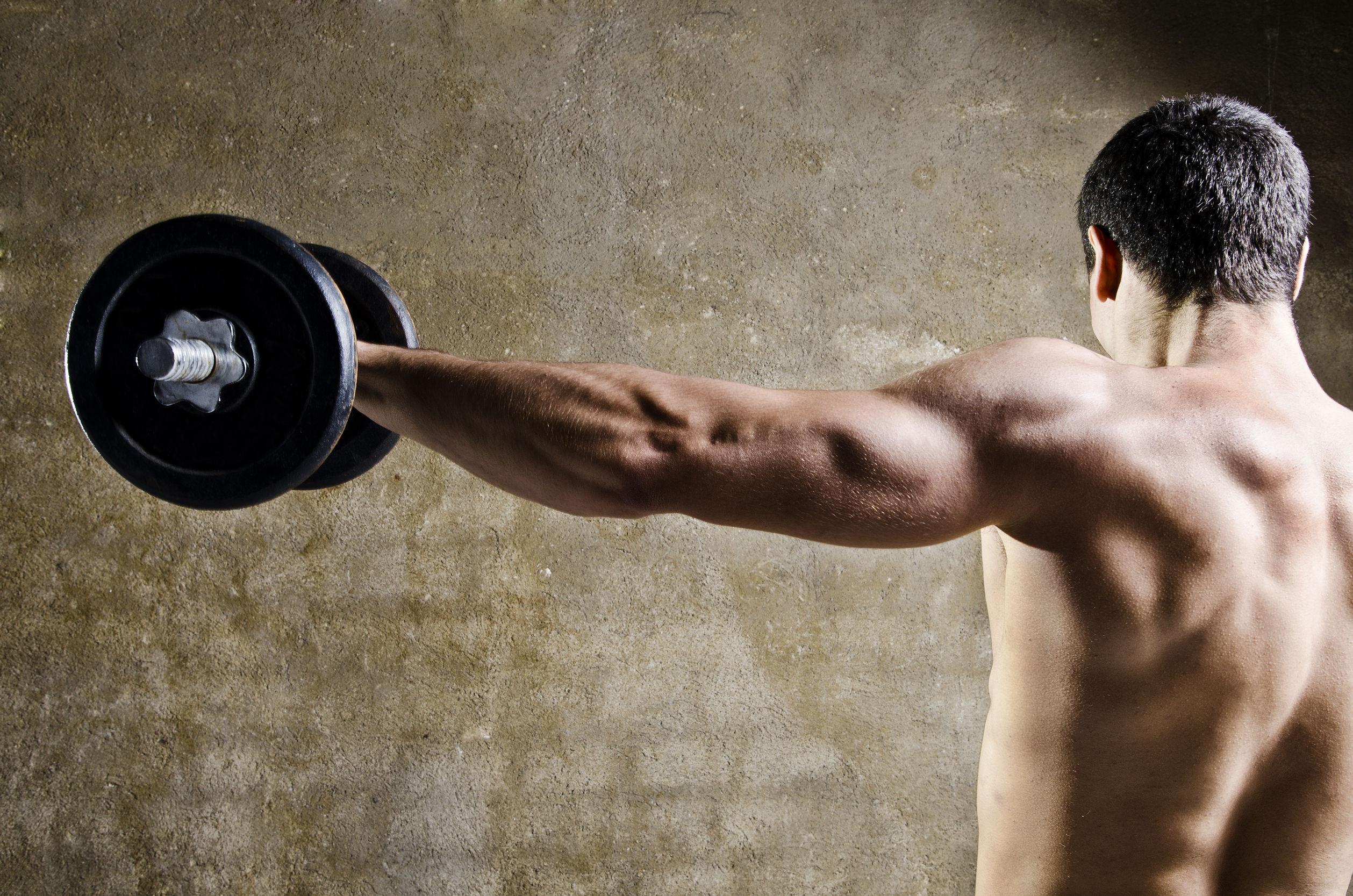 hombre de levantamiento de pesas en frente de la pared