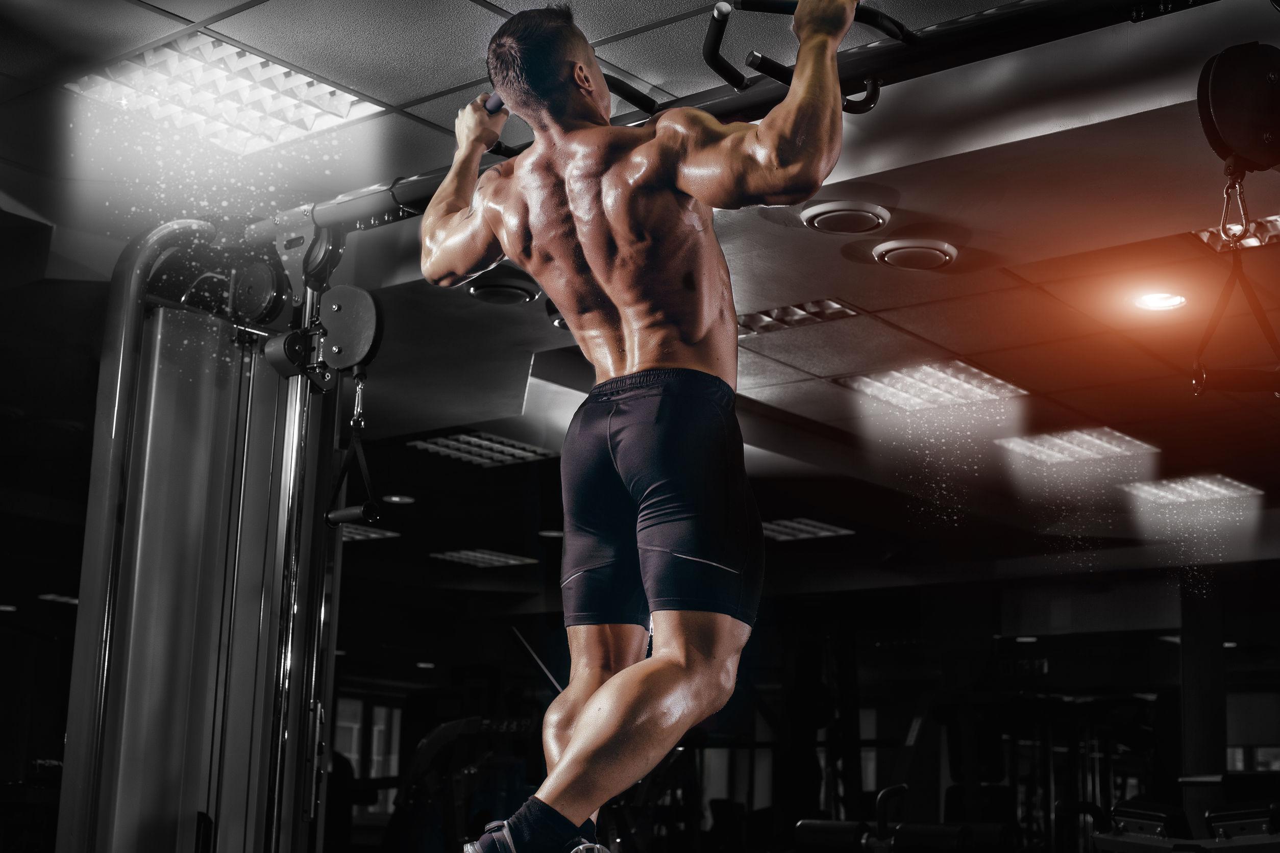 Hombre del músculo atleta en el gimnasio haciendo elevaciones.