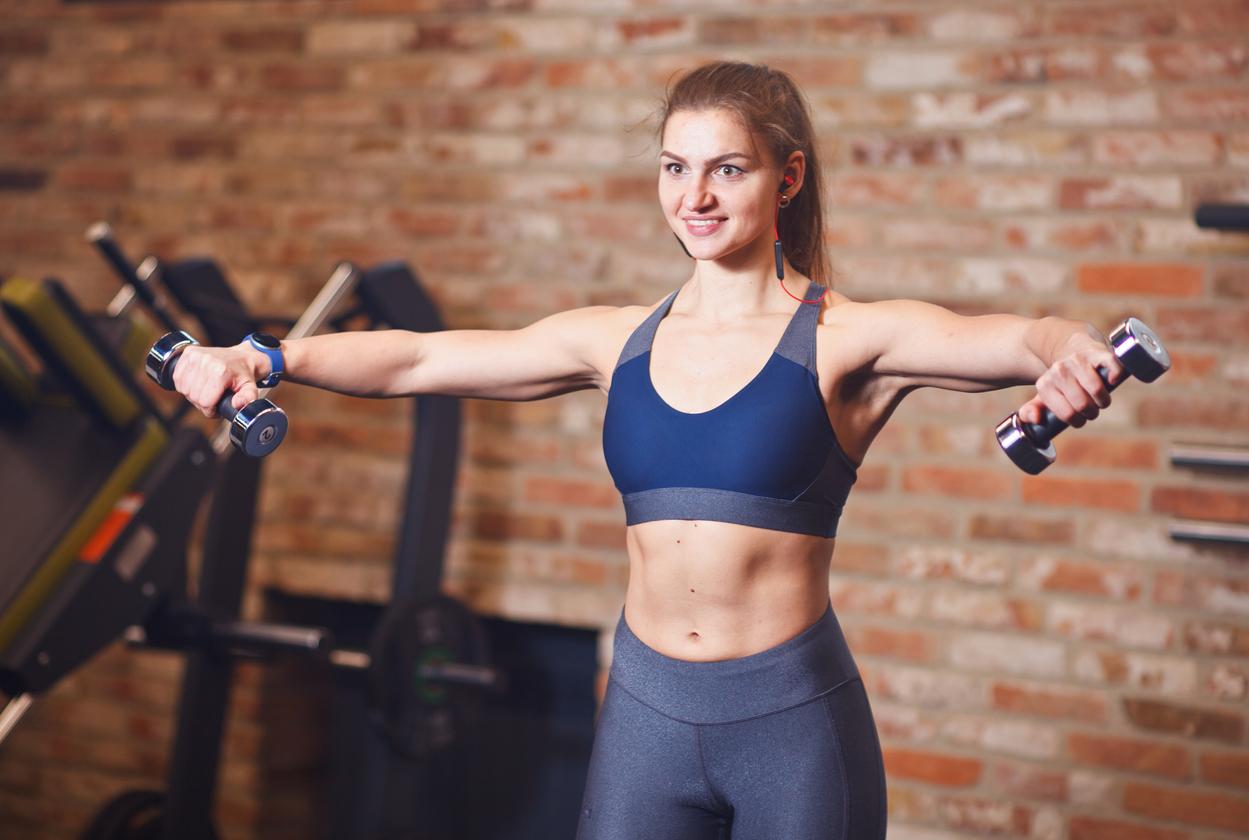 Mujer levantando pesas en gimnasio