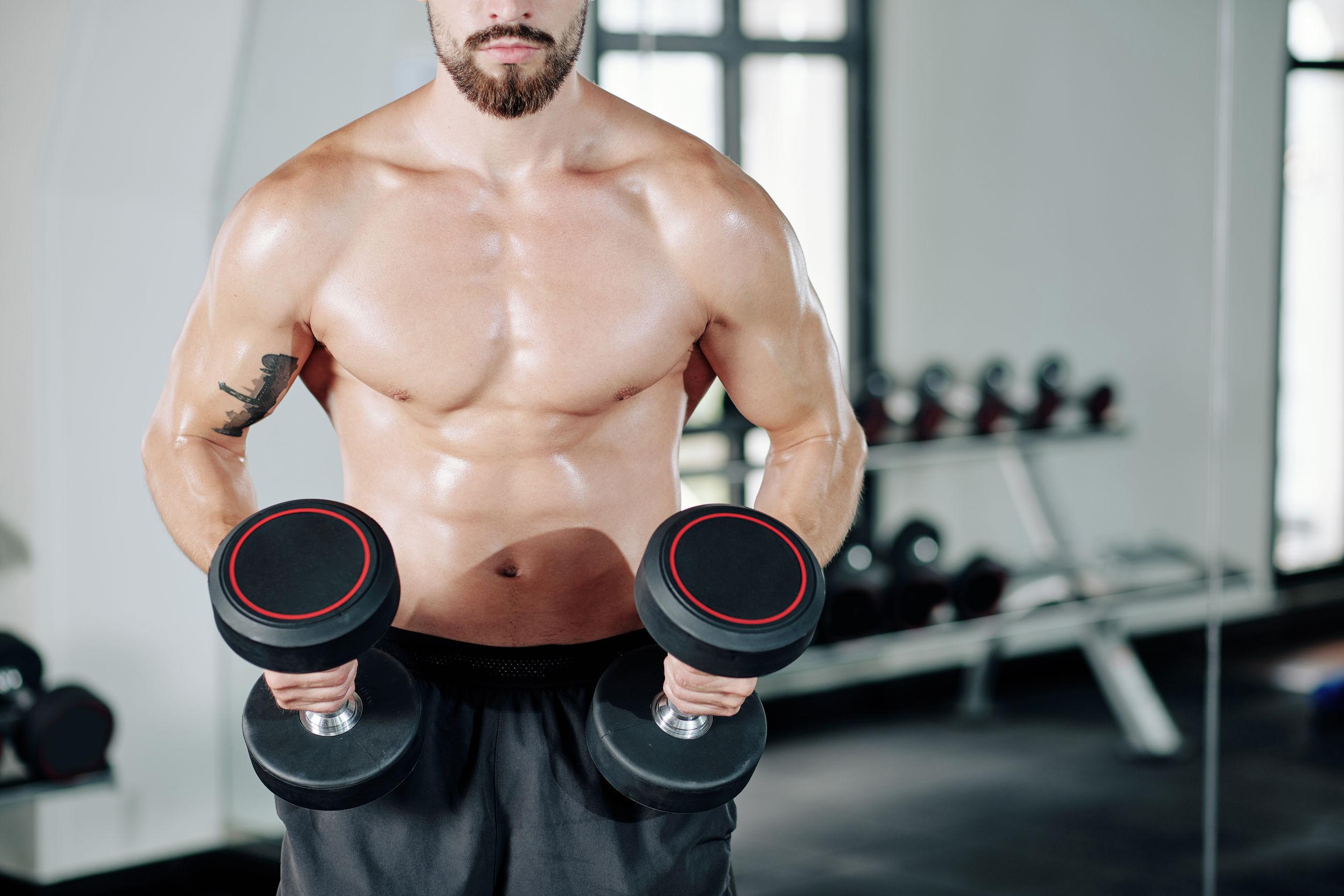 Hombre en gimnasio sosteniendo mancuernas