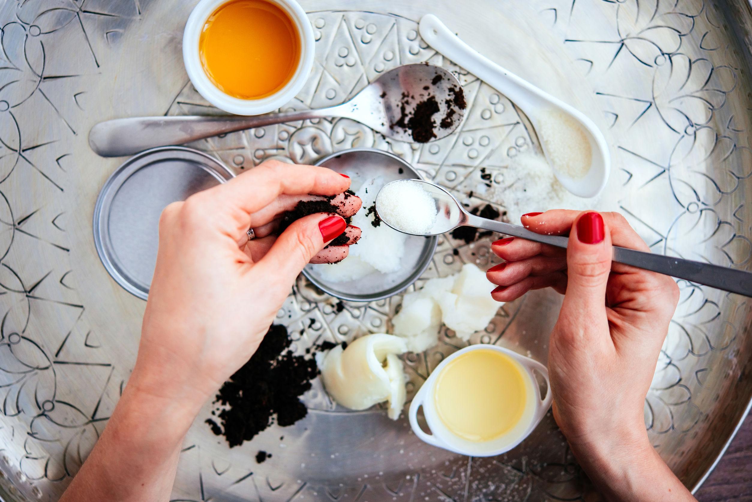 Ingredientes cosméticos hechos a mano - de coco y mantequilla de karité, aceite de oliva, café redonda y azúcar.