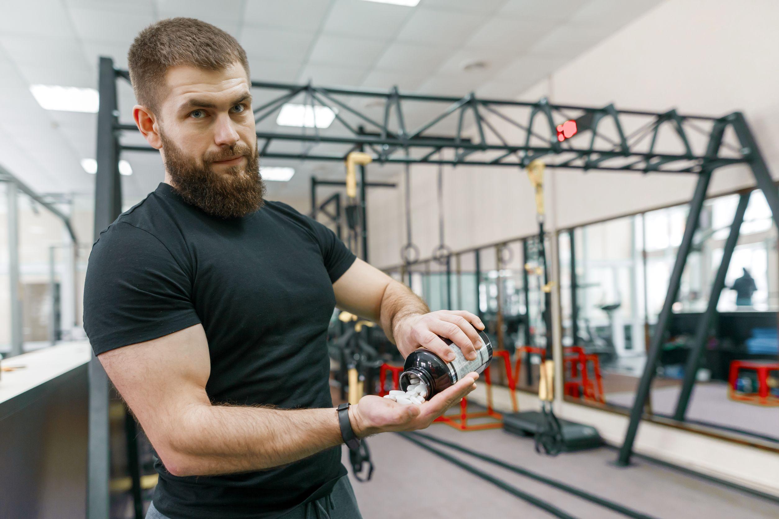 Hombre en gimnasio con bote de vitaminas