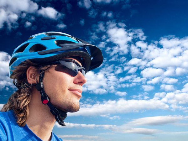 7920159 – portrait of a young bicyclist in helmet and glasses on a sky background