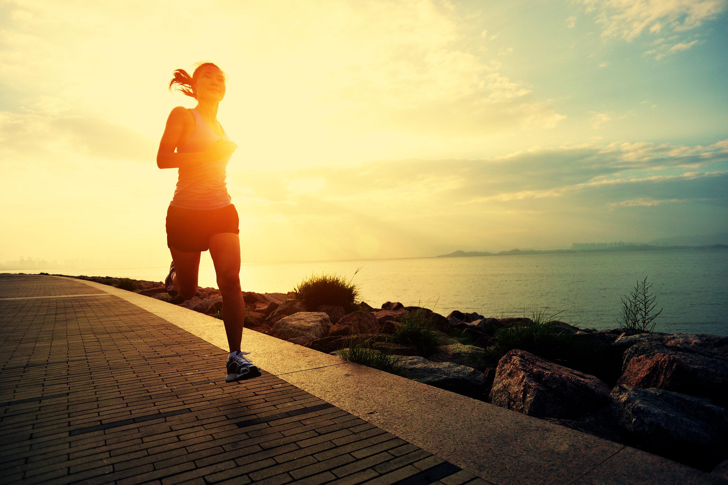 Mujer corriendo al amanecer en la playa