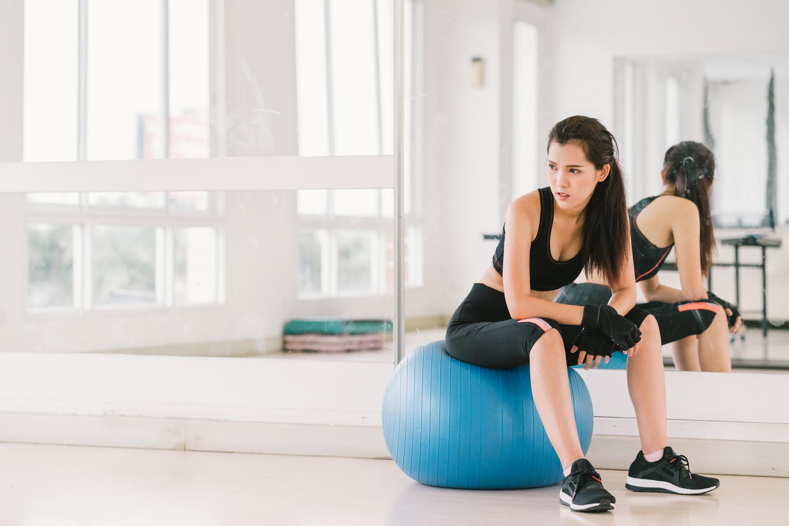 Chica asiática sexy joven y resuelta en bola de la aptitud en el gimnasio