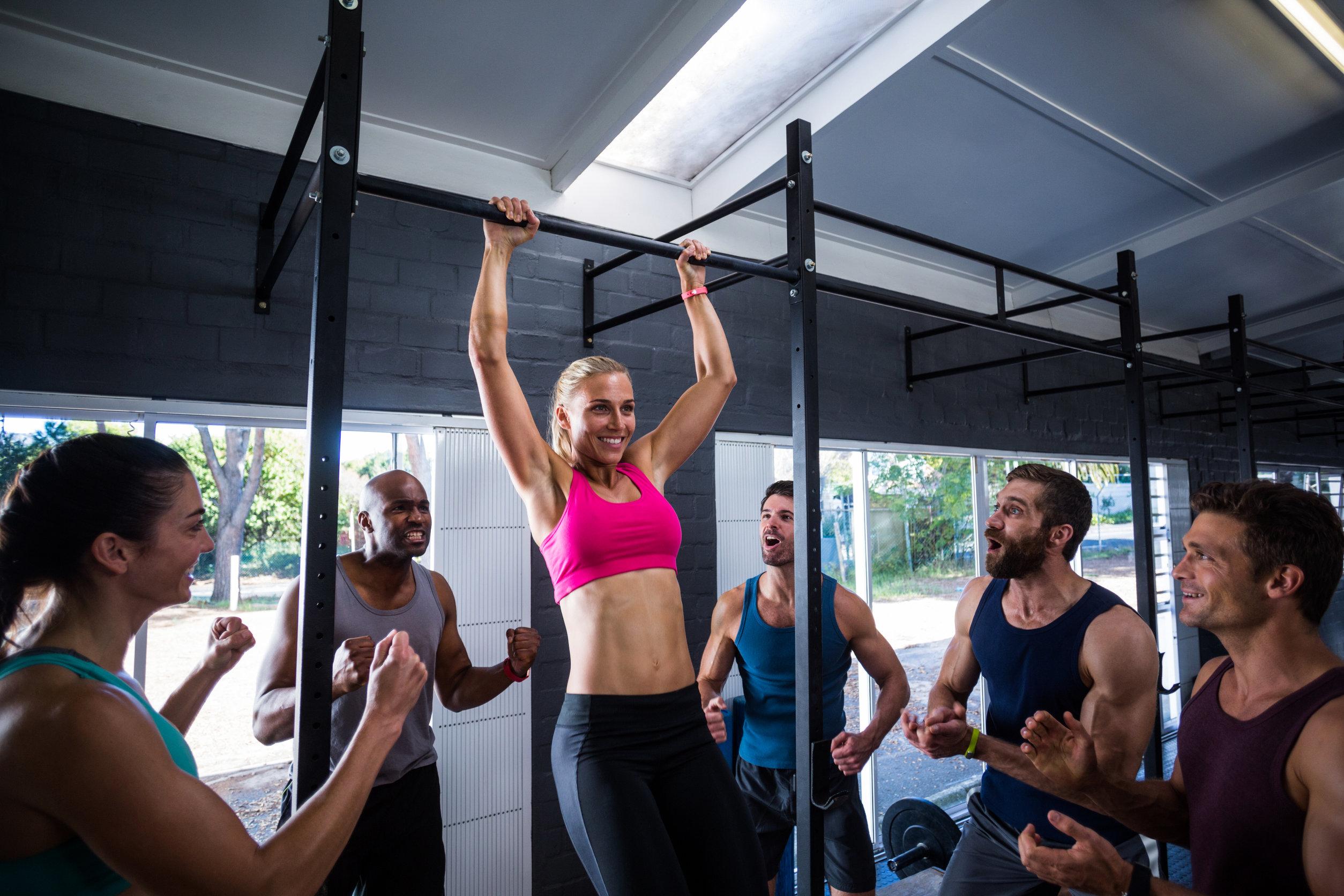 Amigos sonrientes animando a mujer haciendo dominadas en el gimnasio
