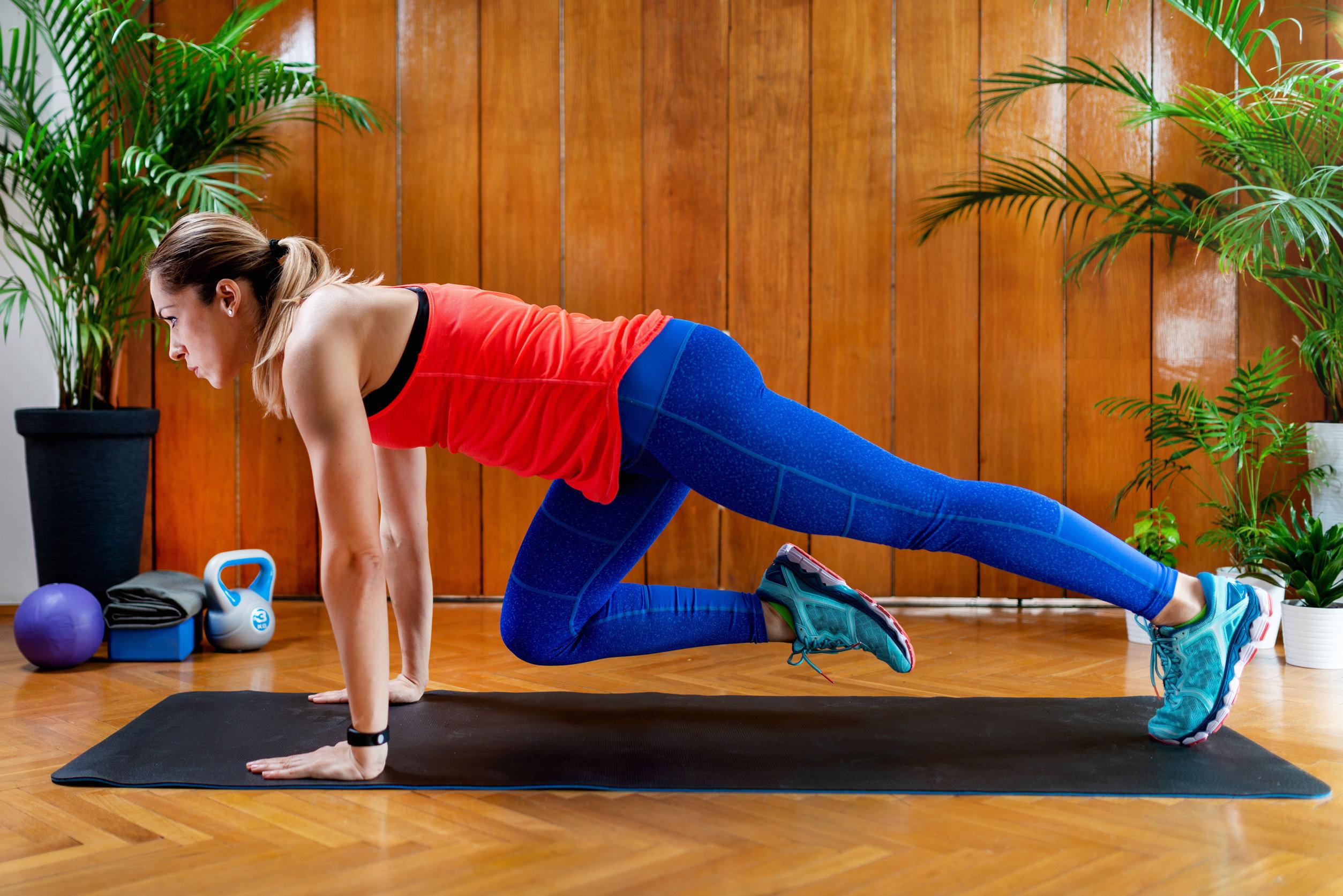Mujer haciendo escaladores en el entrenamiento de intervalos de alta intensidad en casa