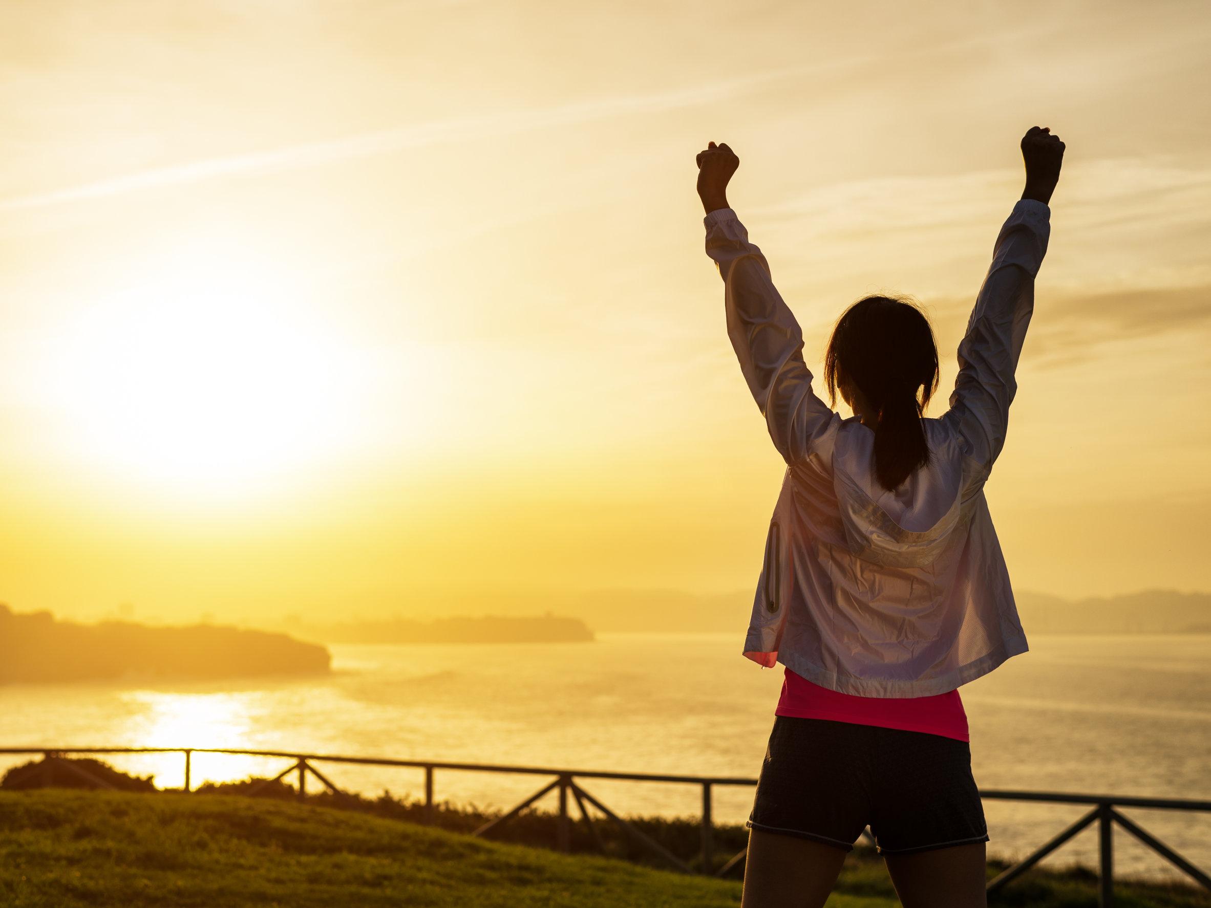 Mujer deportiva exitosa levantando los brazos hacia el mar y la hermosa puesta de sol dorada.