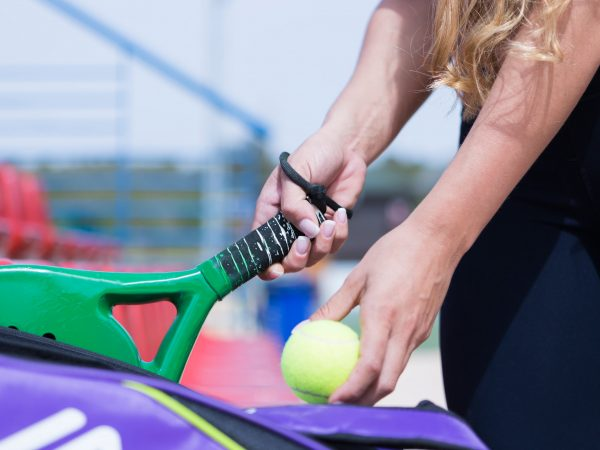 closeup of the hands of a woman taking a paddle racket off from the cover at the paddle tennis court – focus on the handle