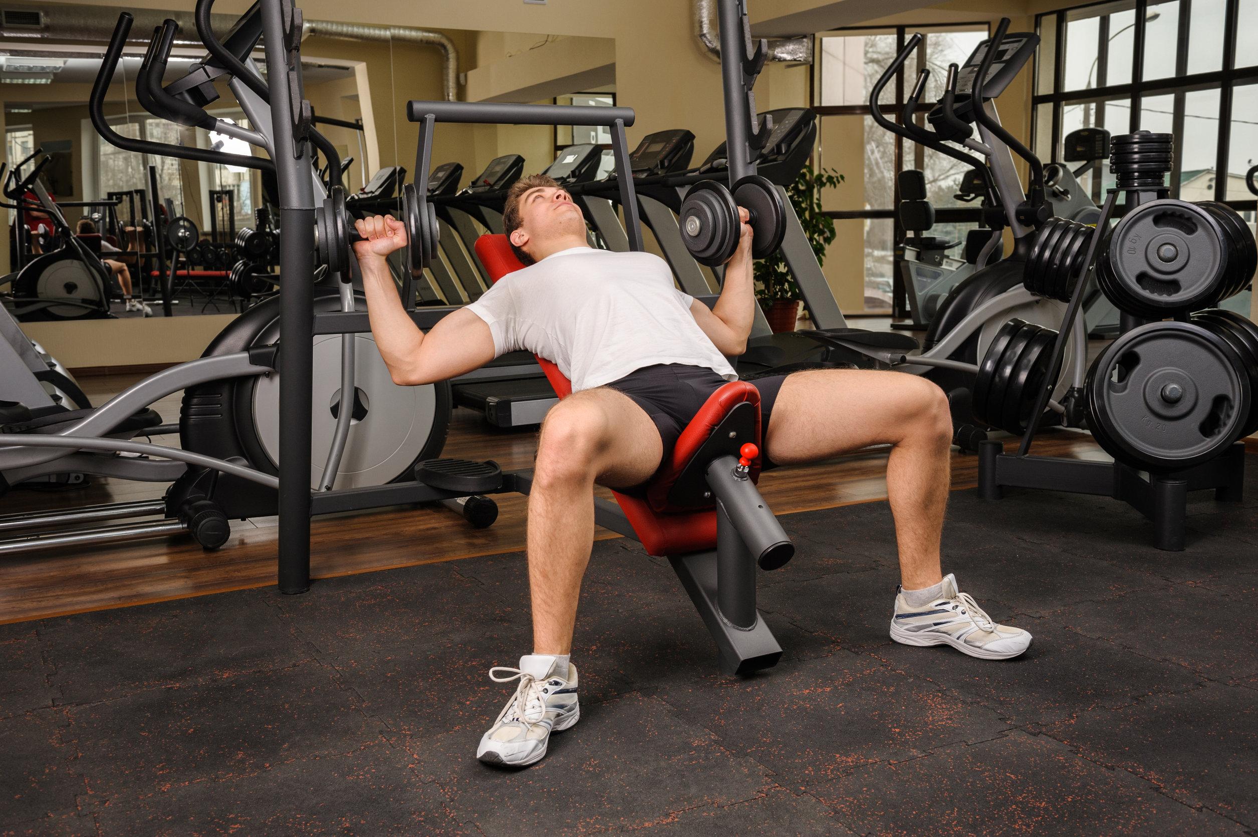 Apuesto joven haciendo ejercicios de press de banca inclinado con mancuernas en el gimnasio