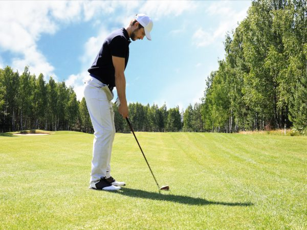Full length of golf player playing golf on sunny day. Professional male golfer taking shot on golf course