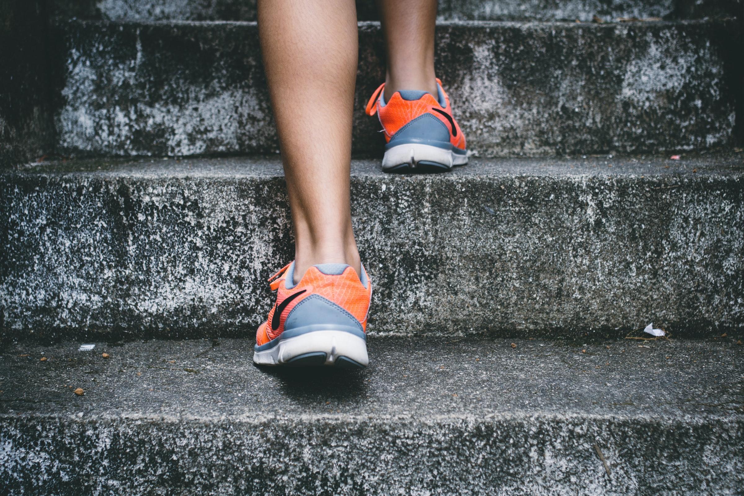 Imagen de persona con zapatos tenis subiendo gradas