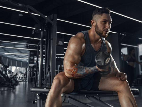 Confident. Young muscular caucasian athlete practicing in gym with the weights. Male model doing strength exercises, training his upper body. Wellness, healthy lifestyle, bodybuilding concept.