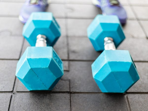 a pair of blue dumbbells on a rubber floor in the home gym, new normal