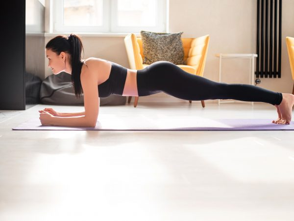 Beautiful strong woman in sport clothes standing in plank position on yoga mat. Active brunette doing abs exercises while staying at home.