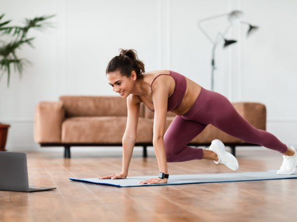 Smiling Sporty Woman Training At Home In Living Room In Front Of Laptop, Beautiful Female Doing Cross Body Mountain Climbers Exercise Looking At Screen Having Online Video Call With Trainer Instructor