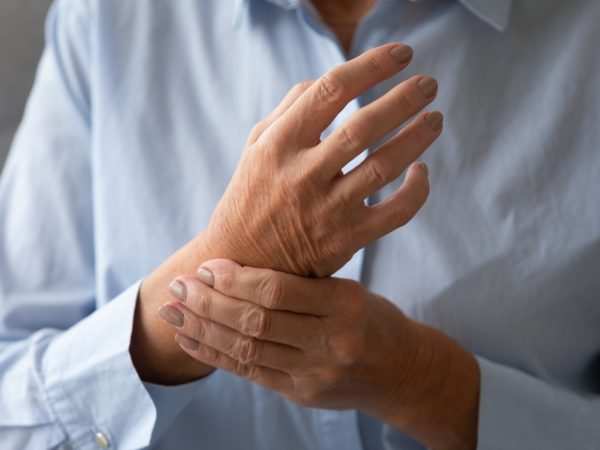 Senior lady massaging hand suffering from rheumatoid arthritis concept, old adult female patient touching wrist feeling hurt joint pain having osteoarthritis disease health problem, close up view