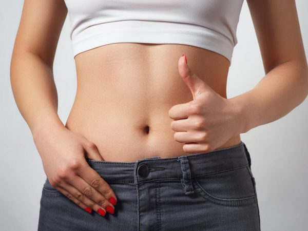 slim, athletic waist of a young woman on white background. The hand in the foreground shows a finger up gesture. the concept of female beauty and health, nutrition and diet, a beautiful figure