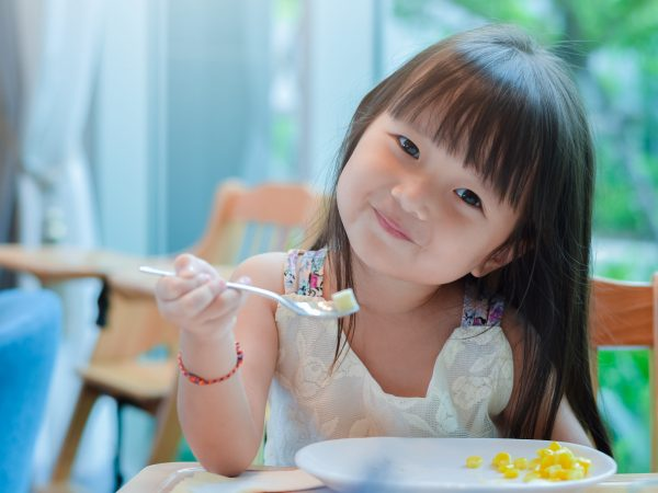 Little asian child girl having breakfast at the morning with a happy smiling face and showing food on a spoon