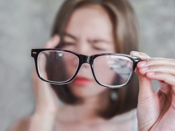 Asian woman holding eyeglasses having problem with eye blur vision